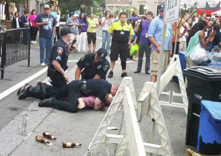 Stamford police officers detain a man who brought beer into the Alive@Five concert on Thursday, July 7, 2011. Photo: Scott Gargan