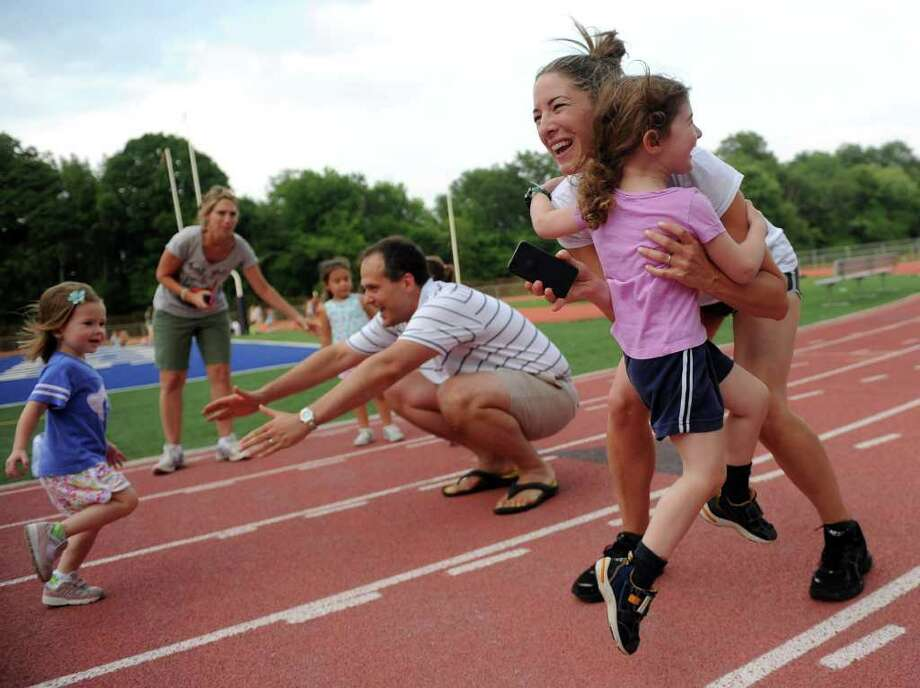 Stephanie Katz picks up her daughter, Nina, as Rob Winslow's daughter, Abby, runs into his arms during Thursday's Westport Age Group Track Meet at Staples High School on July 7, 2011. Photo: Lindsay Niegelberg / Connecticut Post