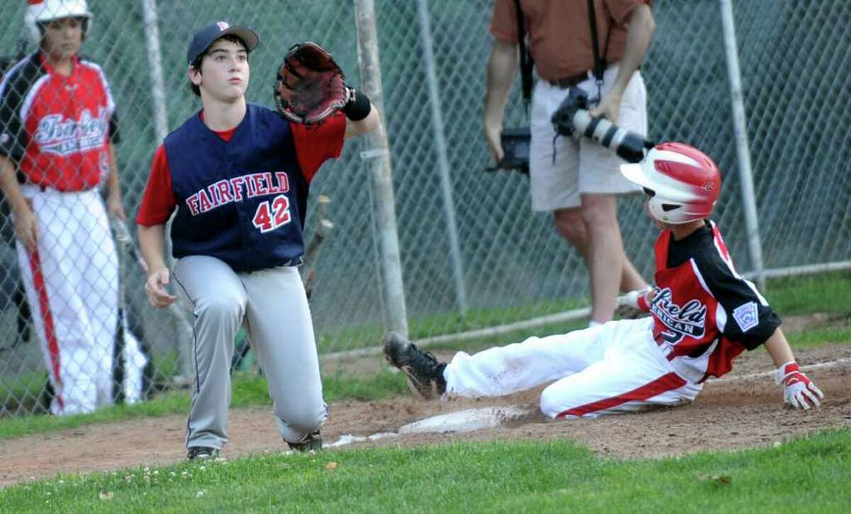 Fairfield National's Jack Cohen waits for the ball as Fairfield American's Connor Lynch slides to third during the District 2 Little League tournament game Tuesday, July 12, 2011 at Blackham School in Bridgeport, Conn.