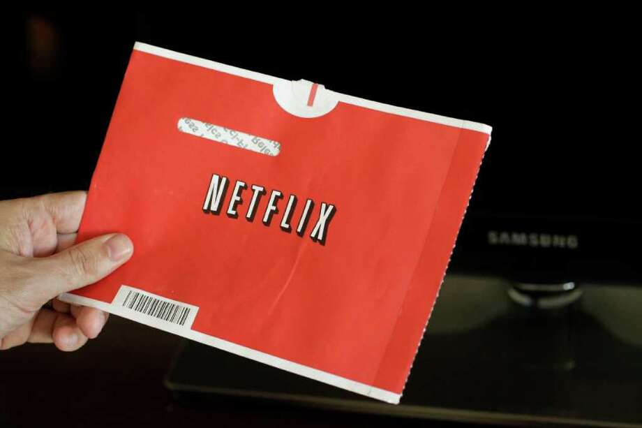 FILE - In this file photo made July 20, 2010, a Netflix customer holds up a movie in Palo Alto, Calif. Netflix Inc. announced Tuesday, July 12, 2011, it is launching new unlimited DVD-only plans in the U.S. at their lowest price ever- only $7.99 a month for the 1 DVD out at-a-time plan and $11.99 a month for the 2 DVDs out at-a-time plan.(AP Photo/Paul Sakuma, file) Photo: Paul Sakuma, STF / AP2010