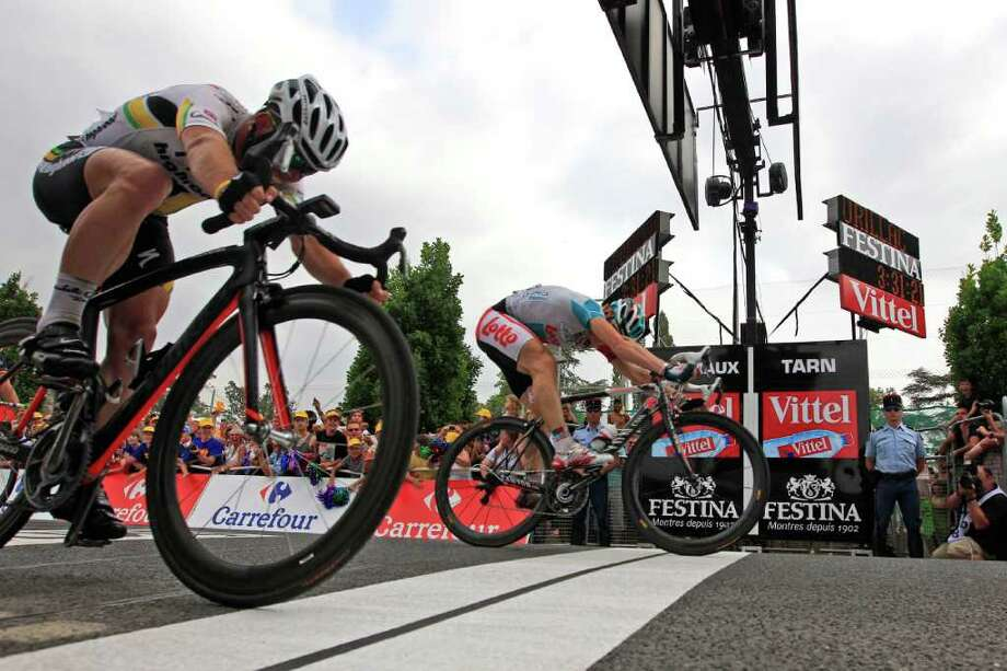 Andre Greipel of Germany, rear, pushes his wheel over the finish line ahead of second place Mark Cavendish of Britain, left, to win the 10th stage of the Tour de France cycling race over 158 kilometers (98.2 miles) starting in Aurillac and finishing in Carmaux, south central France, Tuesday July 12, 2011. (AP Photo/Peter Dejong) Photo: Peter Dejong, STF / AP