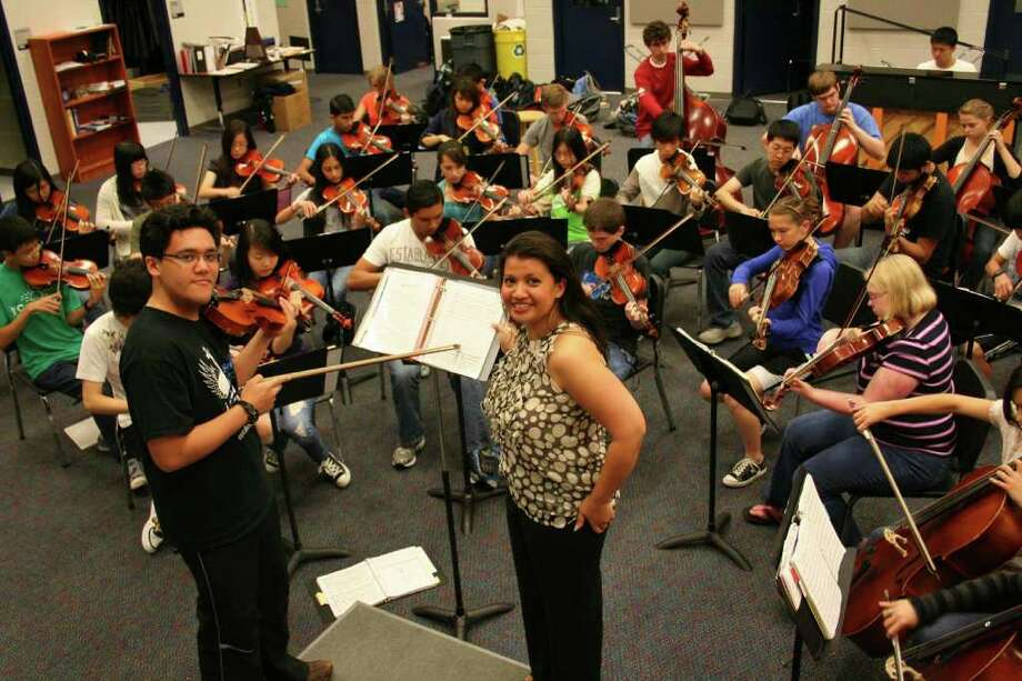 """Seven Lakes HS 2010 graduate R.J. Cruz (left) works with Seven Lakes HS orchestra director Desiree Overree and members of the Seven Lakes HS orchestra.  Cruz wrote an original piece of music, """"Guardian Souls of the Alamo,"""" that was recently recognized with an Honorable Mention Certificate in the 2010 Original Score Contest presented by State Farm Photo: Courtesy"""