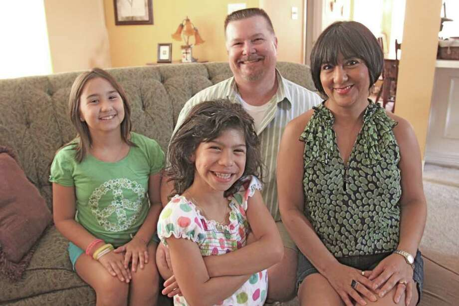 The Rich family, sitting behind, from left, Ava, 10, her dad, John, 48, and in front, from left, her sister, Lila, 8, her mom, Tess, 47.  Lila is a second grader at Hutsell Elementary and has Williams Syndrome.  Suzanne Rehak/Freelance photographer for the Chronicle Photo: Suzanne Rehak, Freelance Photographer
