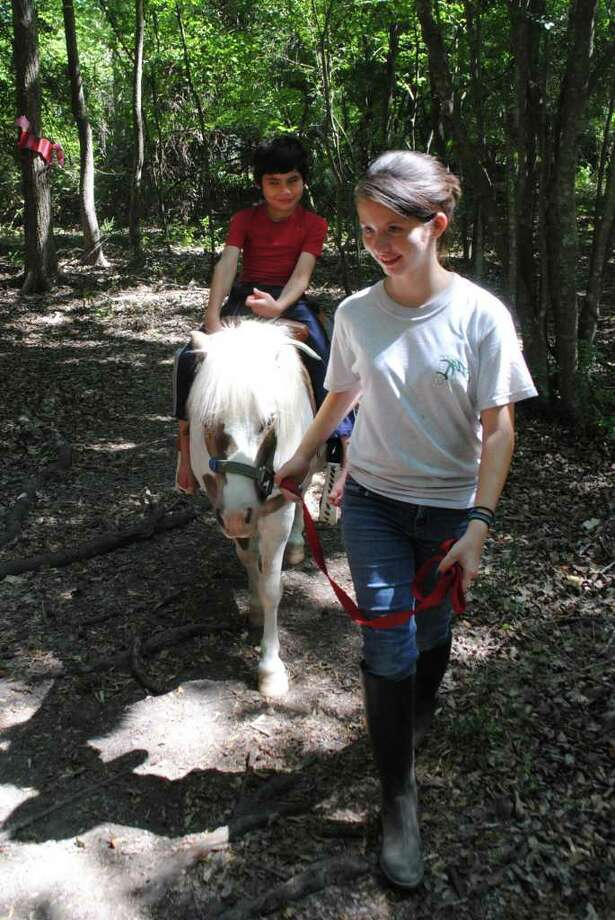 MAKING A DIFFERENCE: Allyson Henry, 15, leads Big Cowboy, carrying Jorge Andres Cabrera, 7, through a trail at Halter Inc. The nonprofit uses miniature horses and other animals to help special-needs children. Photo: Dave Schafer: