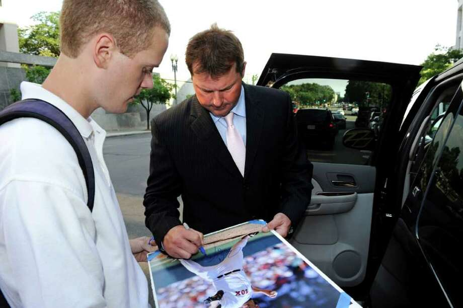 Former Major League Baseball pitcher Roger Clemens signs an autograph for Conor Dotson of Davidson, Md., as he leaves federal court Tuesday, July 12, 2011 in Washington after a day of his trial on charges of lying to Congress in 2008 when he denied ever using performance-enhancing drugs.  (AP Photo/Cliff Owen) Photo: Cliff Owen, FRE / FR170079 AP