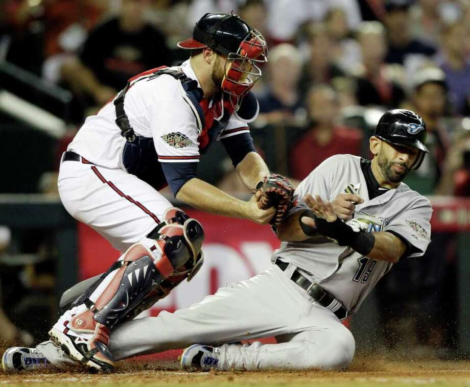 American League's Jose Bautista of the Toronto Blue Jays is tagged out at home plate by National League's Brian McCann of the Atlanta Braves after trying to score on a hit by American League's Adrian Beltre of the Texas Rangers during the fourth inning of the MLB All-Star baseball game Tuesday, July 12, 2011, in Phoenix. (AP Photo/David J. Phillip) Photo: David J. Phillip, STF / AP