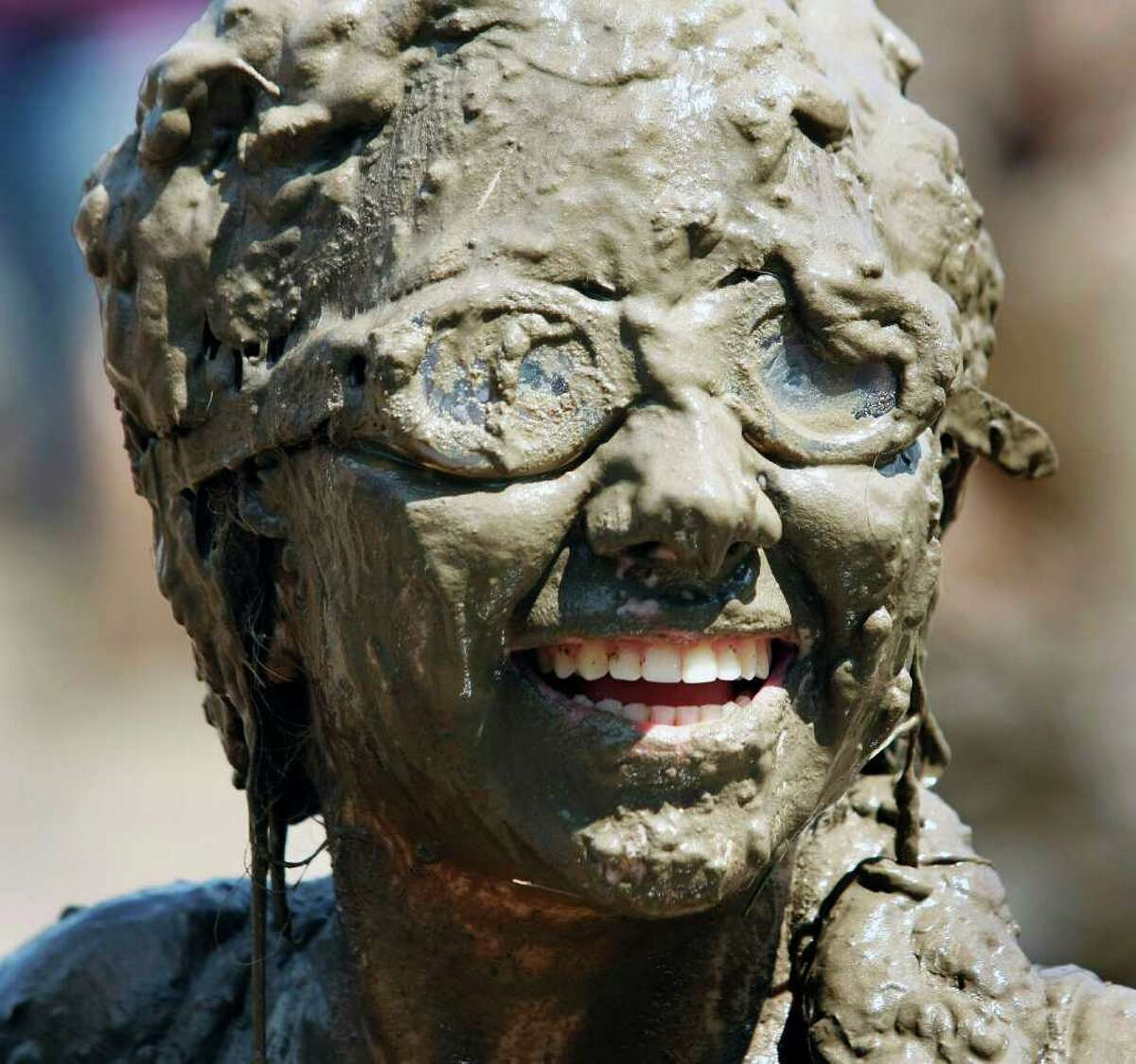 WESTLAND, MI - JULY 12: A girl smiles while covered in mud during Wayne County's 2011 Mud Day event at Nankin Mills Park July 12, 2011 in Westland, Michigan. The annual event consists of 20,000 gallons of water mixed with 200 tons of topsoil. (Photo by Bill Pugliano/Getty Images)