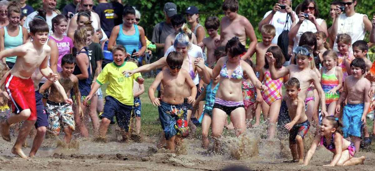 WESTLAND, MI - JULY 12: Children run into a giant lake of mud during Wayne County's 2011 Mud Day event at Nankin Mills Park July 12, 2011 in Westland, Michigan. The annual event consists of 20,000 gallons of water mixed with 200 tons of topsoil. (Photo by Bill Pugliano/Getty Images)
