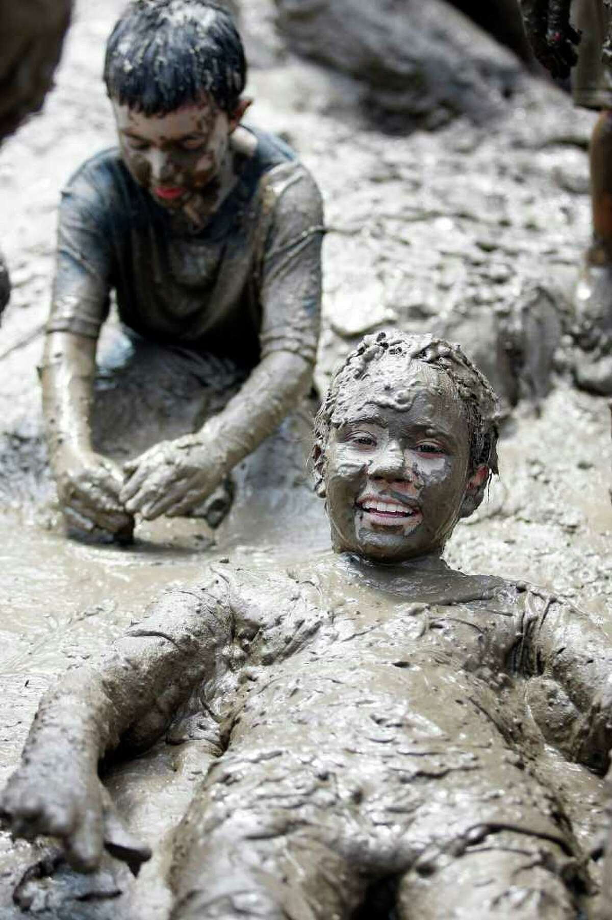 WESTLAND, MI - JULY 12: Children play in a giant lake of mud during Wayne County's 2011 Mud Day event at Nankin Mills Park July 12, 2011 in Westland, Michigan. The annual event consists of 20,000 gallons of water mixed with 200 tons of topsoil. (Photo by Bill Pugliano/Getty Images)