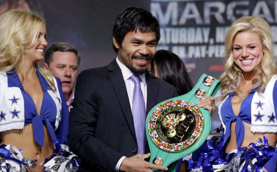 Manny Pacquiao, flanked by Dallas Cowboys cheerleaders,  smiles as he holds the title belt during a news conference Wednesday, Nov. 10, 2010, in Arlington, Texas. Pacquiao is scheduled to fight Antonio Margarito Saturday night at Cowboys Stadium for the WBC World Super Welterweight title. Photo: David J. Phillip, AP / AP