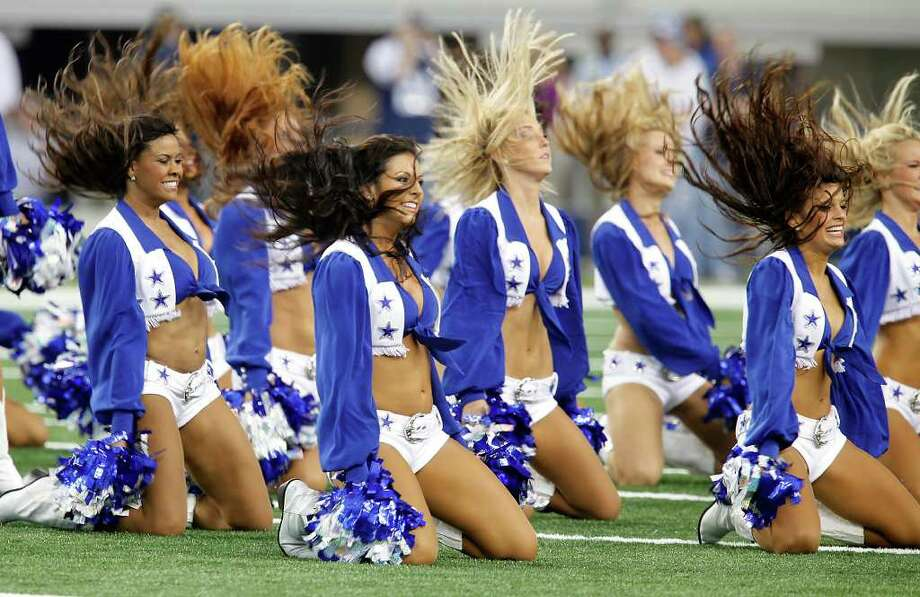 The Dallas Cowboys cheerleaders perform before the Cowboys' pre-season game against the Tennessee Titans at Cowboys Stadium in Arlington on Friday, August 21, 2009. Kin Man Hui/kmhui@express-news.net Photo: Kin Man Hui, San Antonio Express-News / San Antonio Express-News
