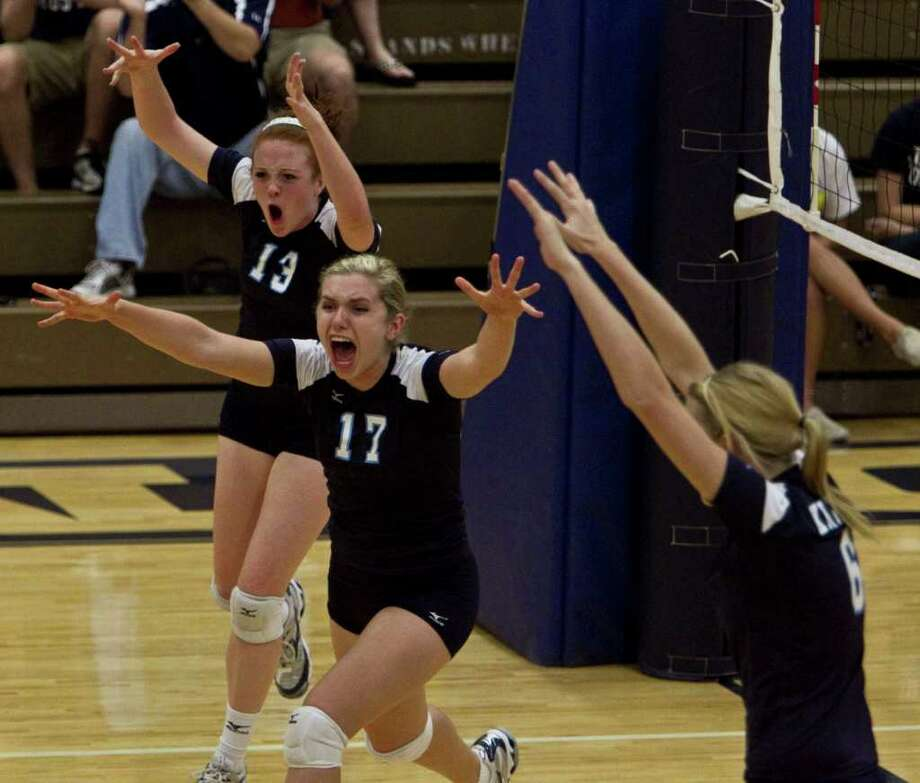 Kingwood's Meredith Rankin (left), Jennifer Groudle (center) and Sara Manifould (right) celebrate after Kingwood scored a point against The Woodlands during high school volleyball game action at Kingwood High School Tuesday, Oct. 19, 2010, in Kingwood. ( James Nielsen / Houston Chronicle ) Photo: James Nielsen, Staff / Houston Chronicle