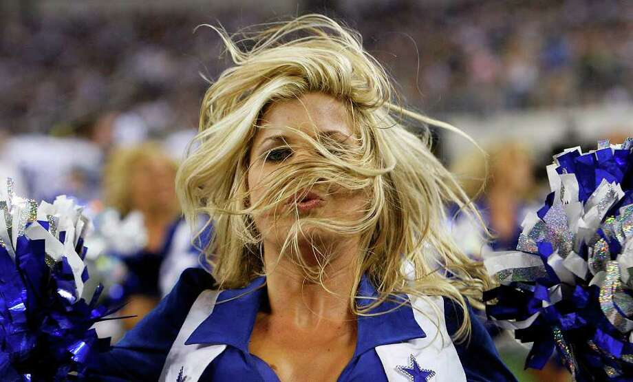 A Dallas Cowboys' cheerleader dances during a pause in the action as the Cowboy went against the Tennessee Titans in a pre-season game at Cowboys Stadium in Arlington on Friday, August 21, 2009. Kin Man Hui/kmhui@express-news.net Photo: Kin Man Hui, San Antonio Express-News / San Antonio Express-News
