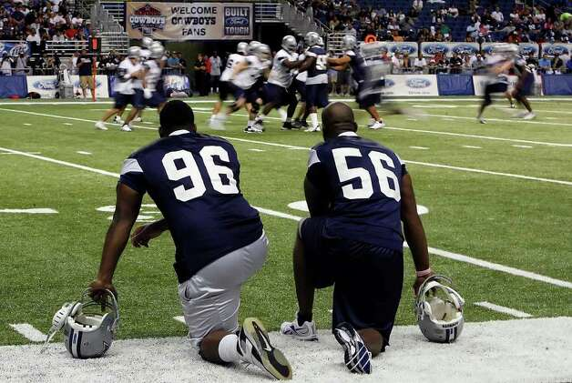 Defensive end Marcus Spears (96) and linebacker Bradie James (56) watch practice from the sidelines on the last day of the Cowboys Training Camp at the Alamodome on Wednesday, August 19, 2009. Kin Man Hui/kmhui@express-news.net Photo: Kin Man Hui, San Antonio Express-News / San Antonio Express-News