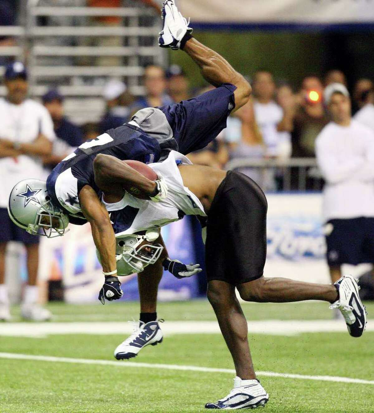 Dallas Cowboys' wide receiver Roy Williams flips Dallas Cowboys' safety Courtney Brown off his back on a pass play during NFL football training camp on Sunday, Aug. 9, 2009 at the Alamodome in San Antonio, Texas. (AP Photo/San Antonio Express-News, Edward A. Ornelas) **RUMBO DE SAN ANTONIO OUT**