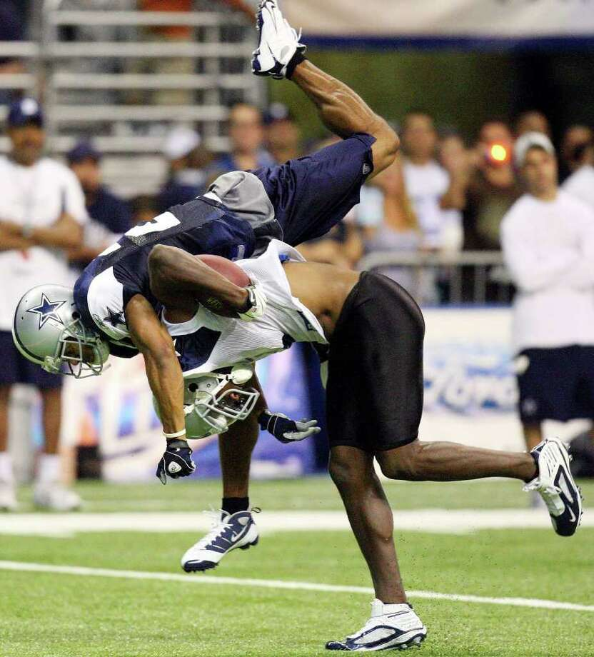 Dallas Cowboys' wide receiver Roy Williams flips safety Courtney Brown off his back on a pass play during 2009's training camp at the Alamodome. Photo: EDWARD A. ORNELAS, AP / SAN ANTONIO EXPRESS-NEWS
