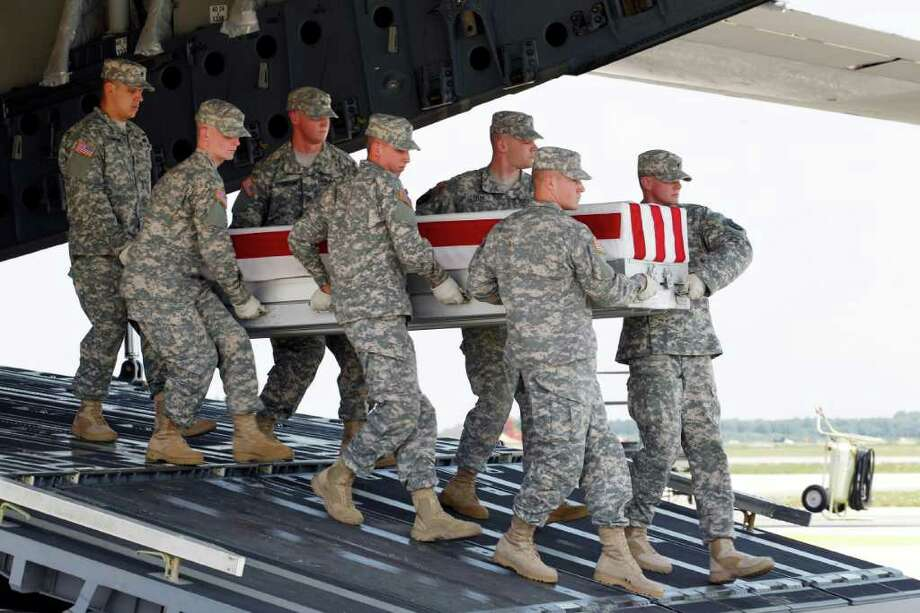 An Army carry team carries the transfer case containing the remains of Army Sgt. Steven L. Talamantez of Laredo Texas, upon arrival at Dover Air Force Base, Del. on Wednesday,  July 13, 2011. The Department of Defense announced the death of Talamantez who was supporting Operation New Dawn in Iraq. Photo: AP