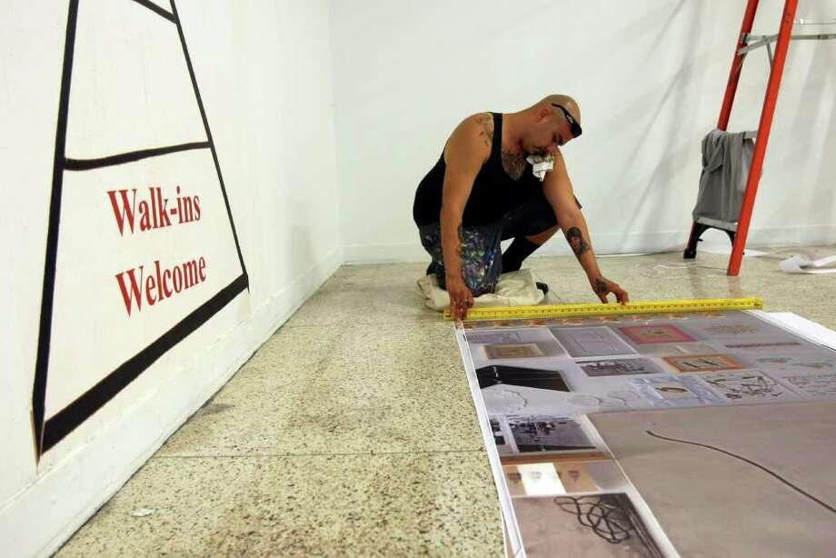 "Enrico ""Caso"" Salinas prepares art work for the Guadalupe Cultural Arts Center exhibit about street art and tattoos. Photo: HELEN L. MONTOYA, HELEN L. MONTOYA/hmontoya@conexionsa.com / SAN ANTONIO EXPRESS-NEWS"