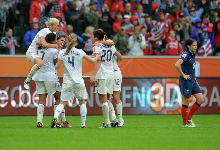 U.S. teammates celebrate after their victory as France's midfielder Elise Bussaglia walks past them after the FIFA women's football World Cup semi-final match France vs the U.S. in Moenchengladbach, western Germany, on Wednesday. The U.S. team won by 1-3 and qualifies for the final.    AFP PHOTO / CHRISTOF STACHE Photo: CHRISTOF STACHE, AFP/Getty Images / 2011 AFP