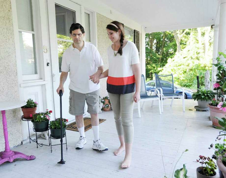 Sydny Grossman, 18, with her father, Ezra Grossman, on the porch of their central Greenwich home, Tuesday night, July 12, 2011. Sydny won a scholarship from the Multiple Sclerosis Society and will be attending American University in Washington, D.C., this year. Her father suffers from multiple sclerosis, which made her eligible for the scholarship. Photo: Bob Luckey / Greenwich Time