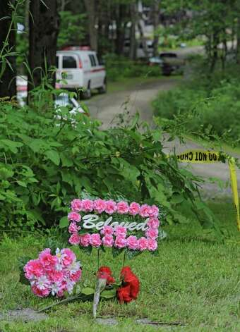 Flowers are left at the end of a driveway on property where authorities said three people were shot to death by Matthew Slocum, who then set the house on fire Wednesday in White Creek. (Lori Van Buren / Times Union) Photo: Lori Van Buren