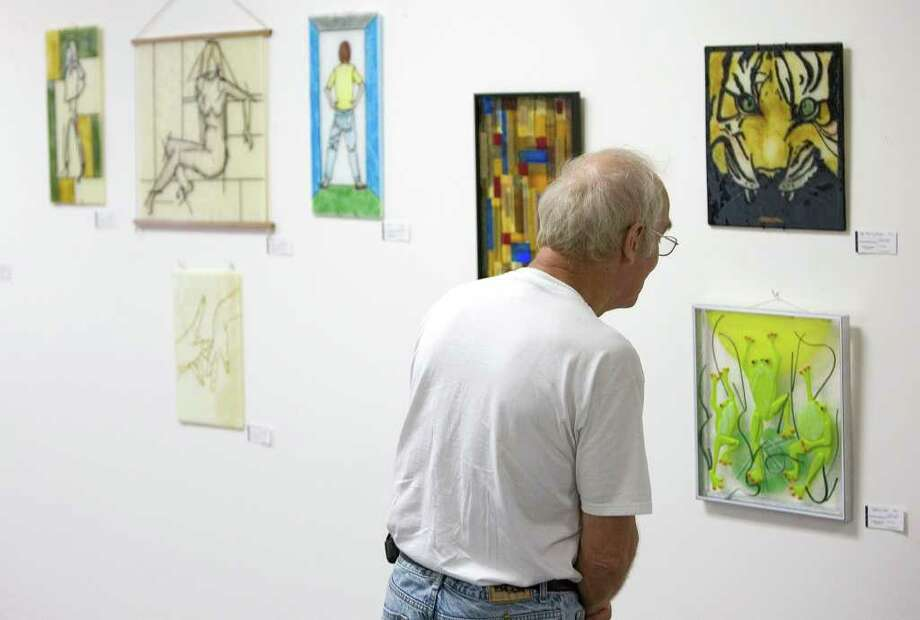 "Bob Scribner, of New Milford, looks at glasswork by Danbury resident Maryann Meken-Silvestri during the opening reception of ""4 Artists - 4 Journeys,"" at Danbury City Hall on Wednesday, July 13, 2011. Photo: Jason Rearick"