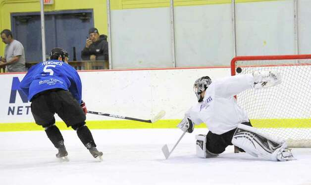 At left, Ryan Hughes of Team Blue scores on Team White goalie, Jonathan Quick, during The Big Assist III hockey game to benefit The Obie Harrington-Howes Foundation at Terry Conners Rink, Stamford, Wednesday night, July 13, 2011. Photo: Bob Luckey / Greenwich Time