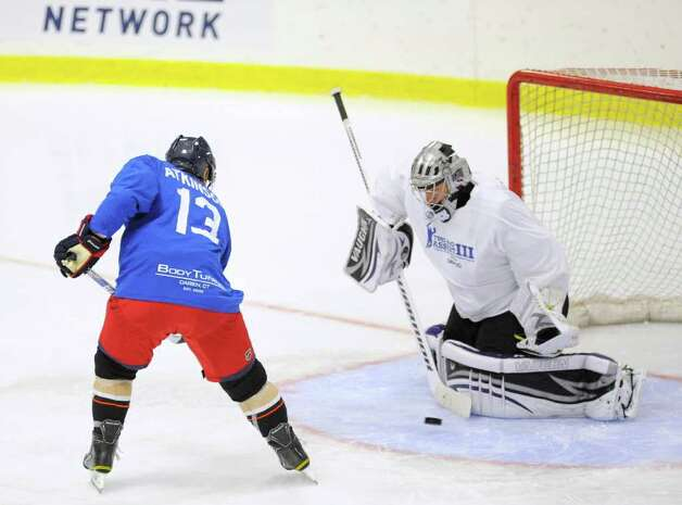 Cam Atkinson, # 13, of Team Blue, left, attempts to deflect the puck past Team White goalie Jonathan Quick during The Big Assist III hockey game to benefit The Obie Harrington-Howes Foundation at Terry Conners Rink, Stamford, Wednesday night, July 13, 2011.  There was no goal on the play. Photo: Bob Luckey / Greenwich Time