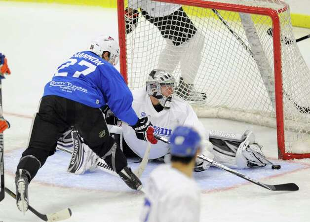 At left, Ryan Shannon of Team Blue, # 27, reaches for the puck as Team White goalie Jonathan Quick makes the stop during The Big Assist III hockey game to benefit The Obie Harrington-Howes Foundation at Terry Conners Rink, Stamford, Wednesday night, July 13, 2011. Photo: Bob Luckey / Greenwich Time