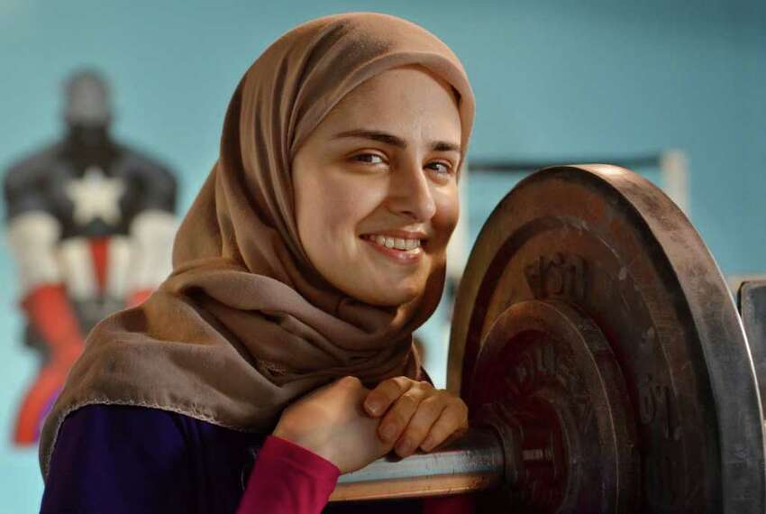 In this photo made Monday, July 11, 2011, Kulsoom Abdullah smiles at Crossfit gym in Atlanta, Ga. Abdullah?'s Ph.D. from Georgia Tech and black belt in taekwondo are proof she doesn?'t back away from challenges. Abdullah on Friday will become the first woman to compete in the national weightlifting championships while wearing clothing that covers her legs, arms and head, in keeping with her Muslim faith. (AP Photo/Joey Ivansco)