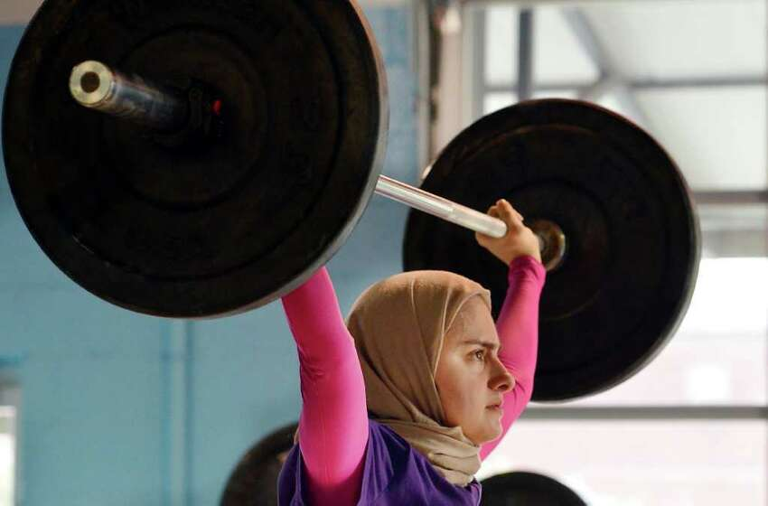 In this photo made Monday, July 11, 2011, Kulsoom Abdullah trains at Crossfit gym in Atlanta, Ga. Abdullah?'s Ph.D. from Georgia Tech and black belt in taekwondo are proof she doesn?'t back away from challenges. Abdullah on Friday will become the first woman to compete in the national weightlifting championships while wearing clothing that covers her legs, arms and head, in keeping with her Muslim faith. (AP Photo/Joey Ivansco)
