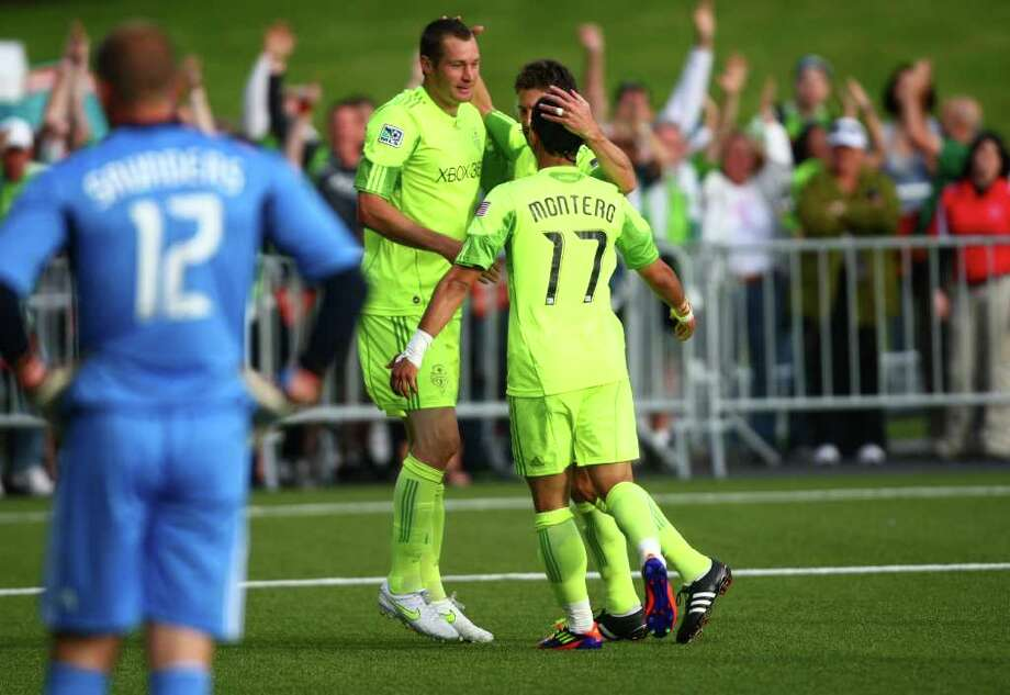 Seattle Sounders player Nate Jaqua, left, gets hugged by teammates Pat Noonan and Fredy Montero, right, as LA Galaxy goalie Josh Saunders looks on after Jaqua scored a goal during the first half of a U.S. Open Cup quarterfinal match at Starfire Sports Complex in Tukwila on Wednesday, July 13, 2011. The Sounders defeated the Galaxy 3-1. Photo: JOSHUA TRUJILLO / SEATTLEPI.COM
