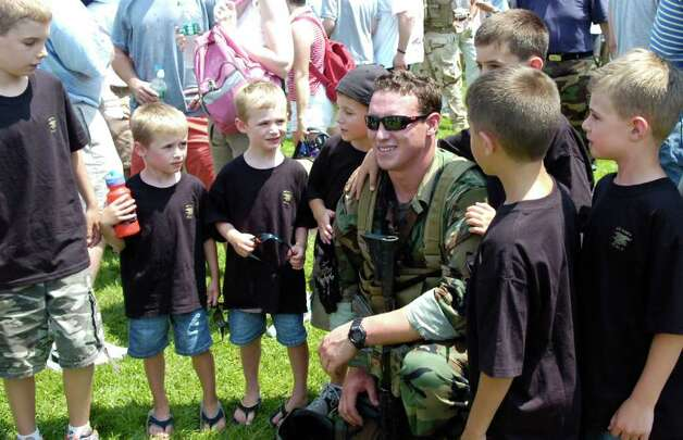 GHS graduate and Navy SEAL Carl Higbie takes center stage with a group of kids that will be his nieces and nephews after he is married next week to GHS sweetheart Kaitlyn Caruso. Higbie took part in the SEAL's demonstration at the Annual Salute to Veterans. Photo: File Photo / Greenwich Time File Photo