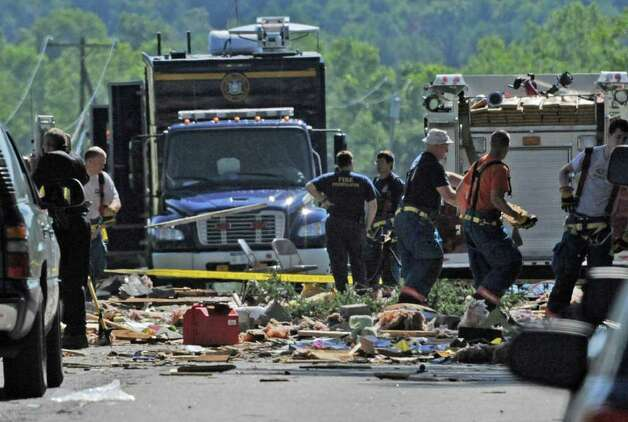 Investigators and firefighters comb the explosion site Thursday morning July 14, 2011 on Route 29 in Salem, N.Y. for clues as the investigation continues in to how 4 people were killed and 7 were injured Wednesday at 4372 Route 29.  (Skip Dickstein / Times Union) Photo: SKIP DICKSTEIN / 2011