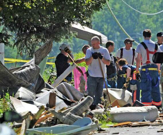 Investigators and firefighters comb the explosion site Thursday morning July 14, 2011 on Route 29 in Salem, N.Y., for clues as the investigation continues in to how 4 people were killed and 7 were injured  Wednesday  at 4372 Route 29.  (Skip Dickstein / Times Union) Photo: SKIP DICKSTEIN / 2011