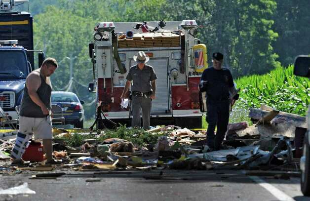 Investigators and firefighters comb the explosion site Thursday July 14, 2011 on Route 29 in Salem, N.Y., for clues as the investigation continues in to how 4 people were killed and 7 were injured Wednesday at 4372 Route 29.  (Skip Dickstein / Times Union) Photo: SKIP DICKSTEIN / 2011