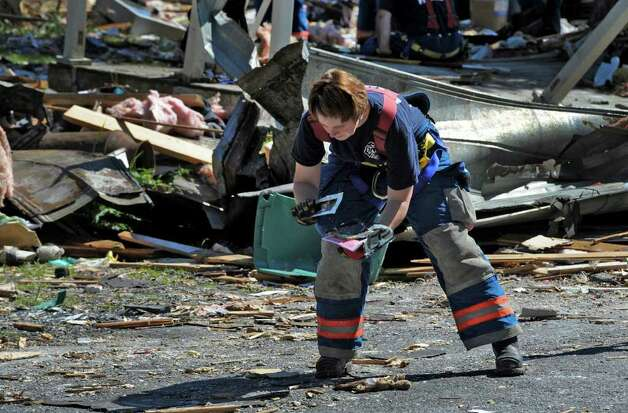 A firefighter picks up personal items including photos at the explosion site on Thursday morning July 14, 2011 Route 29 in Salem, N.Y., for clues as the investigation continues in to how 4 people were killed and 7 were injured yesterday at 4372 Route 29.  (Skip Dickstein / Times Union) Photo: SKIP DICKSTEIN / 2011