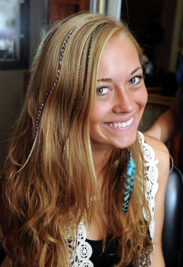 Kaitlyn Brophy, 18, of Newtown, regularly stops by Robert Anthony's Salon in Newtown for feather hair extensions. Photo taken Wednesday, July 13, 2011. Photo: Carol Kaliff
