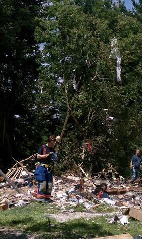 Investigators at the scene of a house explosion in Salem, Washington County, collect photos found inside the foundation where the house once stood on Thursday, July 14, 2011. (Leigh Hornbeck/Times Union)