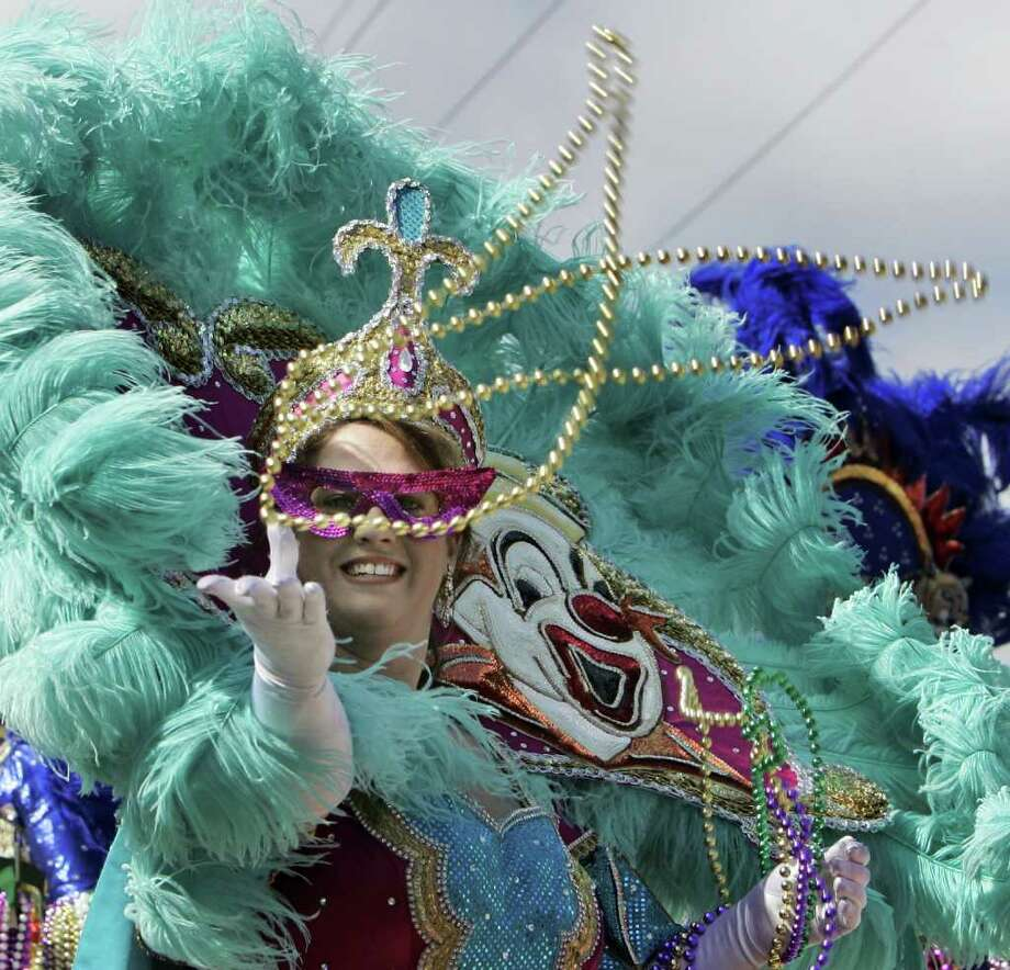 This Feb. 2, 2008 file photo shows a masked rider throwing beads during the Krewe of Iris Mardi Gras parade in New Orleans. There may not be parades with colorful floats, but you can still be part of the Mardi Gras fun though you're miles away from Bourbon Street.     (AP Photo/Alex Brandon) Photo: Alex Brandon, File / AP