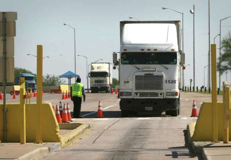 Trucks approach the automated toll plaza going into Mexico at the World Trade Bridge in Laredo. Photo: Bob Owen, San Antonio Express-News / rowen@express-news.net