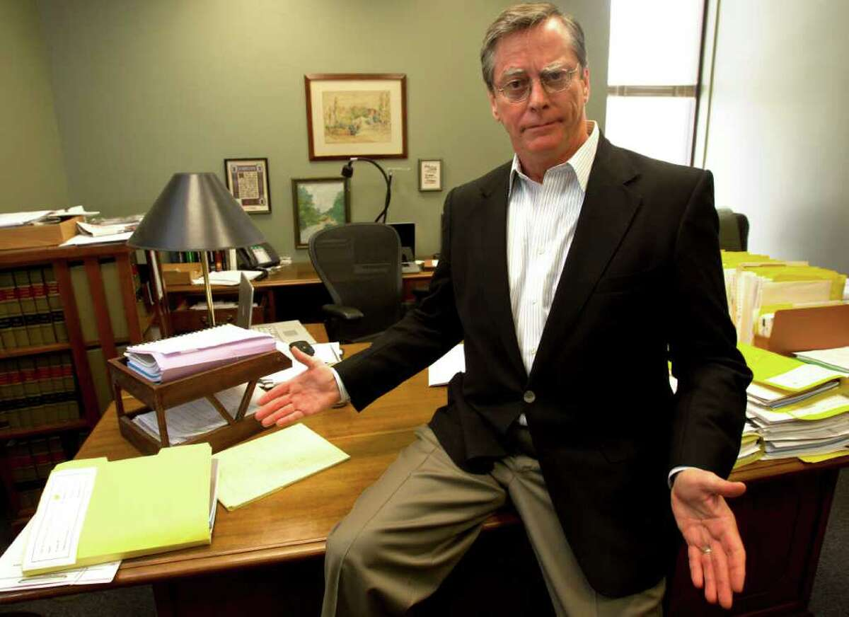 """Texas First Court of Appeals Justice Jim Sharp sits on his desk inside his office at the First Court of Appeals Monday, July 11, 2011, in Houston. Harris County is removing the historic, antique, solid-wood desks and replacing them with brand-new, less solid desks in the historic offices. Sharp's desk previously served a judge in the Galveston Court House before moving to Houston offices. """"Who knows how many judges have sat at this desk over the course of time?"""" Sharp said. """"It's got history."""" ( Cody Duty / Houston Chronicle )"""