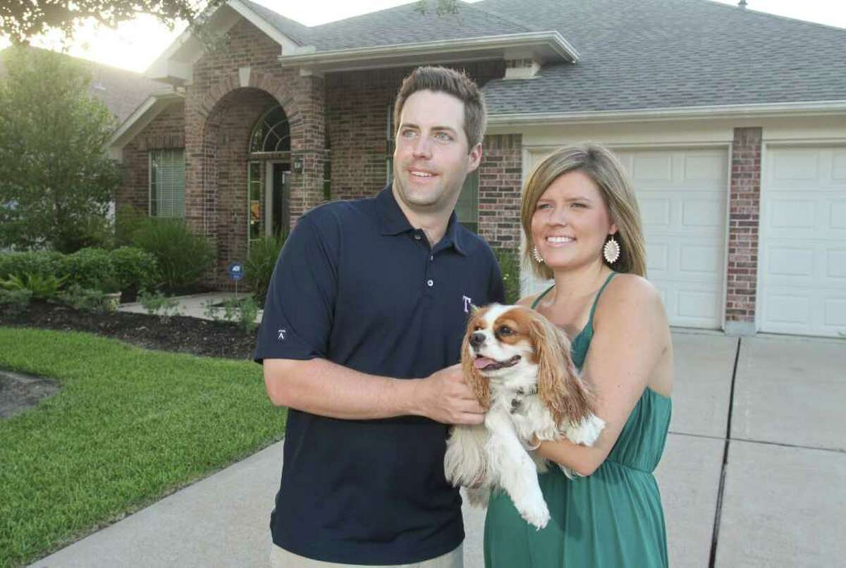 Andie and Ryan Fagala, with their King Charles Cavalier Spaniel, Bella, in front of their home in League City. Click to see the best local suburbs for young professionals.