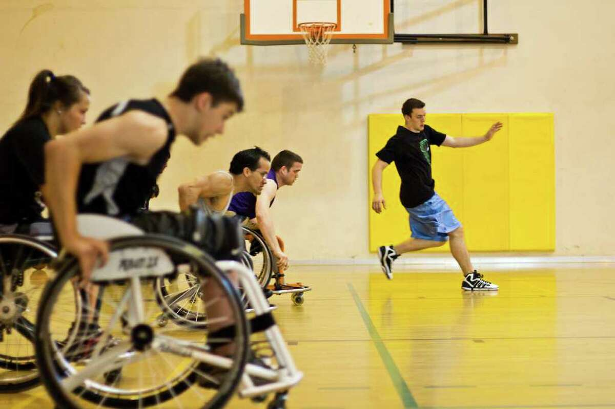 Players follow Head Coach Christian Burkett during speed drills from the base line to the half court line at the Miller Community Center in Seattle's Capitol Hill neighborhood during Drop-In Wheelchair Basketball practice.