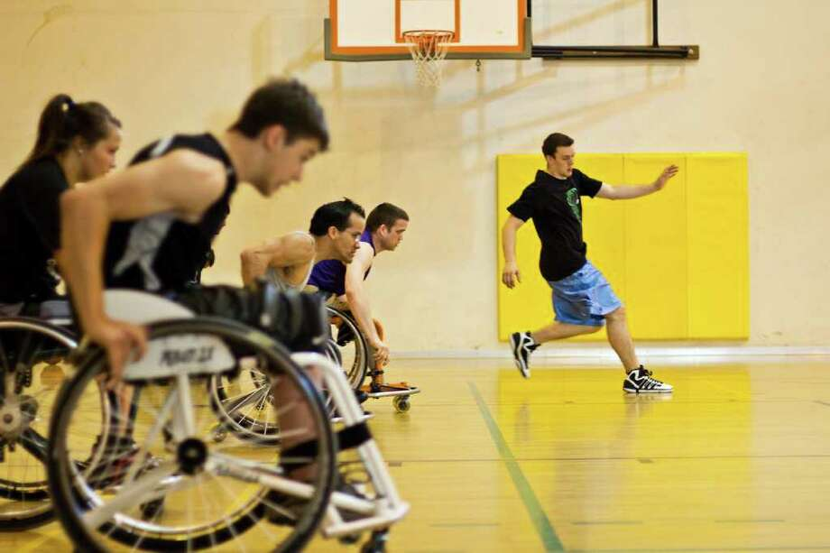 Players follow Head Coach Christian Burkett during speed drills from the base line to the half court line at the Miller Community Center in Seattle's Capitol Hill neighborhood during Drop-In Wheelchair Basketball practice. Photo: JOE DYER / SEATTLEPI.COM