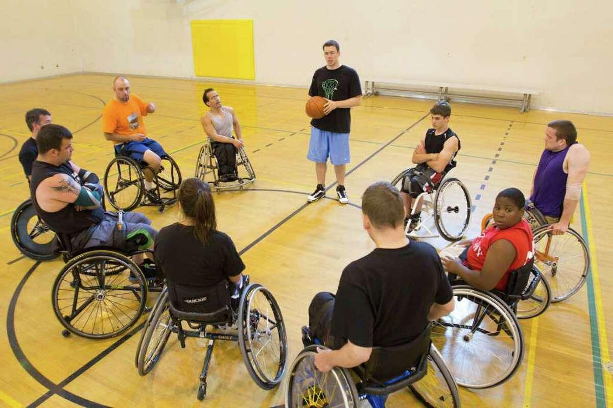 Wheelchair basketball players listen to coach Christian Burkett during practice at Miller Community Center.