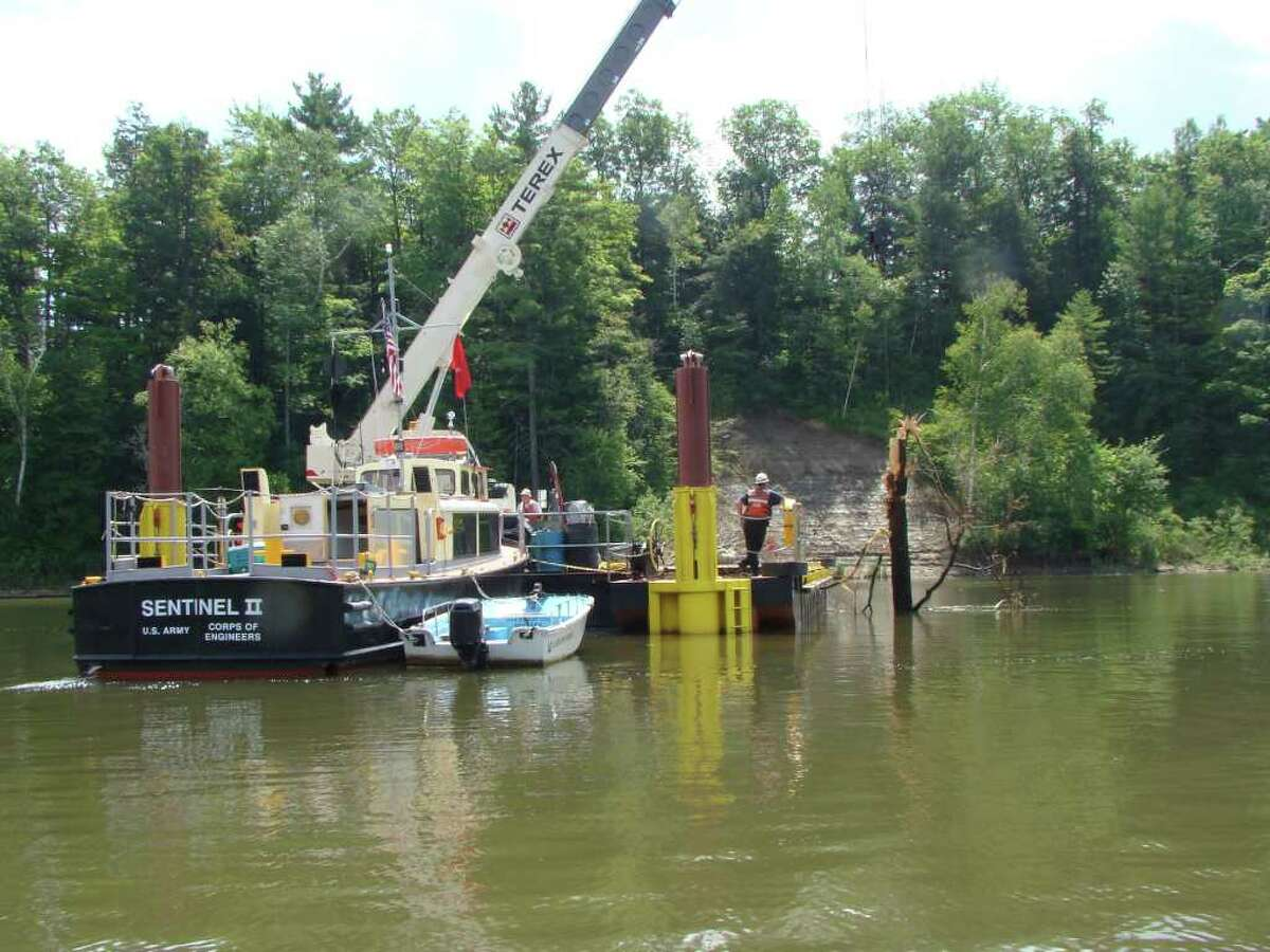 A crew from the U.S. Army Corps of Engineers uses a crane to pull trees and other debris out of the shipping channel of Lake Champlain at the Narrows in the town of Dresden, Washington County, on July 14, 2011 to clear a recent landslide caused by the record flooding around the lake. (Photo courtesy of U.S. Army Corps of Engineers)
