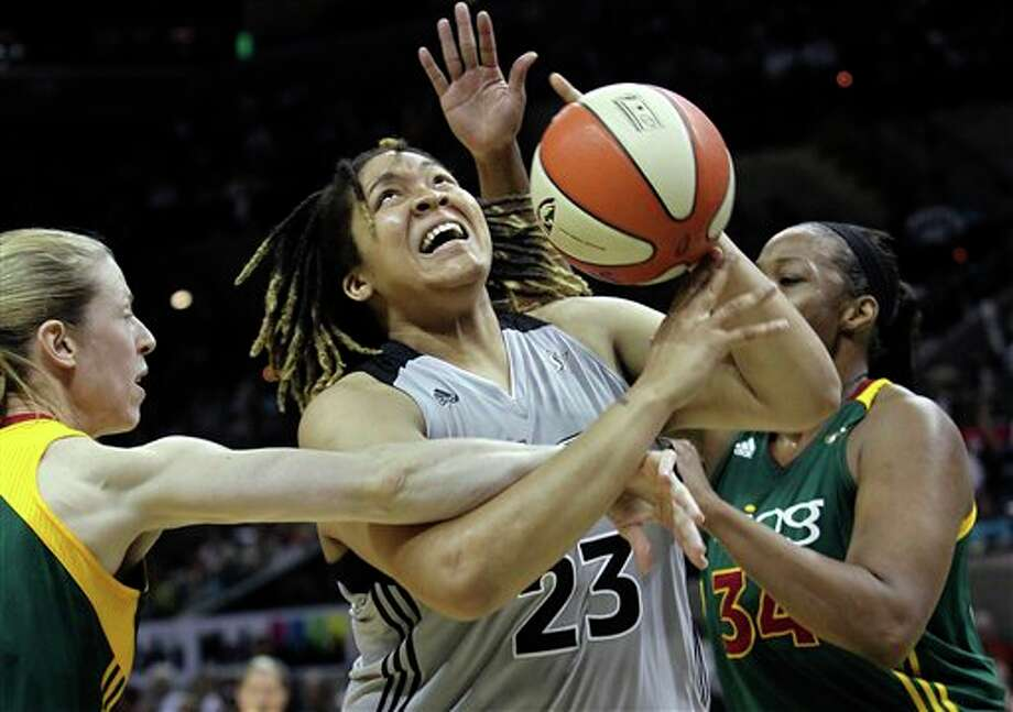 The Silver Stars' Danielle Adams is fouled under the basket as Seattle Storm's Katie Smith (left) and Le'Coe Willingham defend during  on Thursday at the AT&T Center. TOM REEL/treel@express-news.net Photo: Express-News