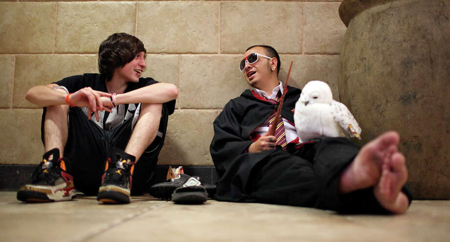 "Robby Martinez, 19, (left) and Clif Sanchez, 20, as ""Harry Potter,""  relax while waiting for the midnight showing of ""Harry Potter and the  Deathly Hallows: Part 2"" on July 14, 2011, at the Santikos Palladium.  The friends said they arrived at noon for the movie. Photo: Edward A. Ornelas / Express-News"