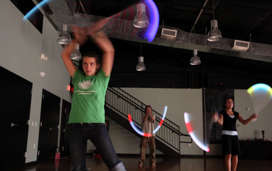 Amanda Gagliano (from left), Steve Smith, and Maritza Benavides spin LED  lighted Poi during class at The Synergy Studio. Photo: Edward A. Ornelas / Express-News / © SAN ANTONIO EXPRESS-NEWS (NFS)